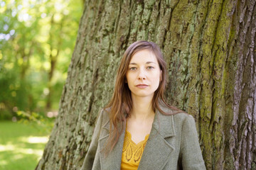Portrait of young woman by tree