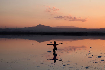A tourist  poses for a photo during the sunset at a salt lake in Larnaca
