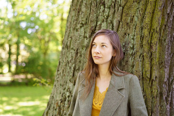 Thoughtful sad young woman leaning on a tree