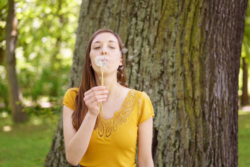 Young woman blowing on a dandelion clock