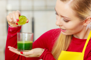 Woman in kitchen holding vegetable juice