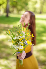 Laughing young woman offering a posy