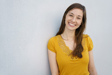 Relaxed smiling young woman leaning on a wall