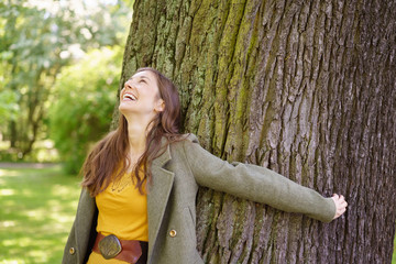 Cheerful young woman embracing tree