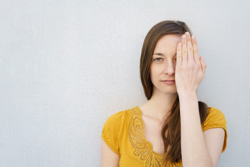 Serious young woman covering one eye