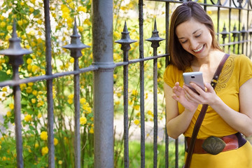 Happy young woman checking her mobile phone
