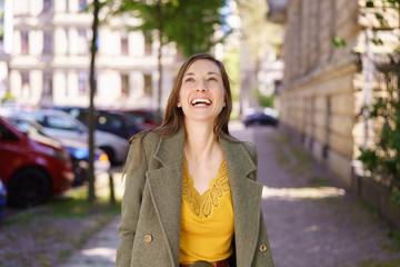 Happy stylish woman walking through town
