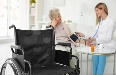 Wheelchair and blurred young nurse measuring blood pressure of elderly woman on background
