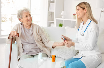 Young nurse examining elderly woman with glucometer at home