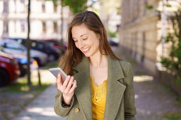 Young woman reading a text message with a smile