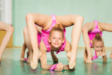 Young girl practicing rhythmic gymnastics in gym