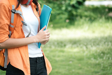 Education and relax outdoor. Girl holding folder and education gadget.