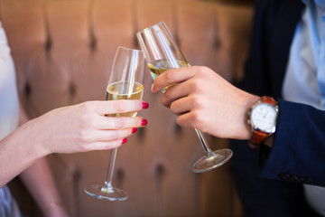 close up of champagne glasses in male and female hands