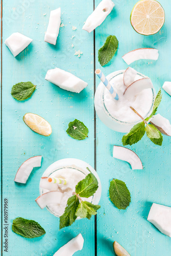 Summer refreshment drinks, cocktails. Frozen coconut mojito with lime and mint. Pina colada. On a light blue green wooden table with ingredients. Copy space top view