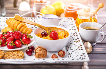 Breakfast with cornflakes berry honey and croissant on wooden