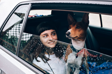 Selective focus shot of pretty young woman and her pet dog, sit together inside a car and look on the rain outside