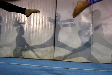 Shadows of gymnasts are cast on a wall in Santiago