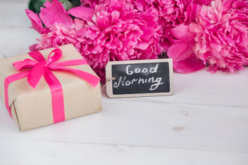 Pink peony flowers,gift box and notes good morning on white rustic table from above, breakfast on Mothers day or Womens day .