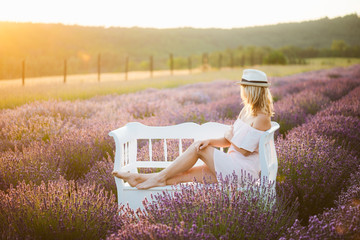 Young beautiful woman enjoy nature. Blonde hair woman relaxing on bench in a lavender field and enjoy sunset.