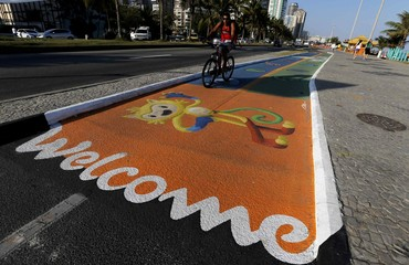 Man rides his bicycle as he passes over a newly-painted bicyle lane ahead of the Rio 2016 Olympic games in Rio de Janeiro