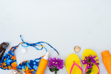 Summer beach fun - border of sandals with glasses, swimming suit and sunscreens