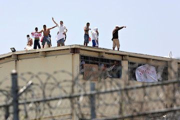 Inmates stand up on the roof of the Topo Chico prison during a massive riot after dozens of prisoners were transferred to other prisons, according to local media, in Monterrey
