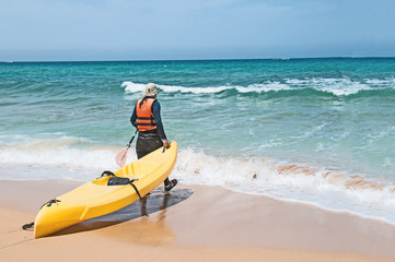 Kayaker pulls a kayak on the sand to the sea