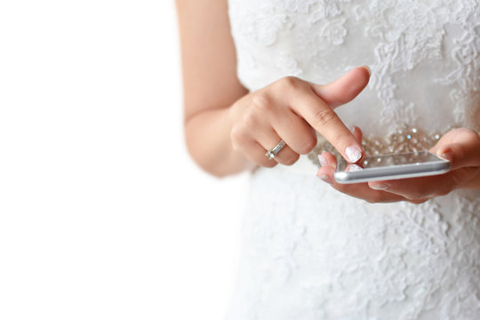 Bride holding modern phone and touching screen, isolated on white background with free space