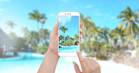 Girl taking picture of pool with smartphone with palm trees and beach in background