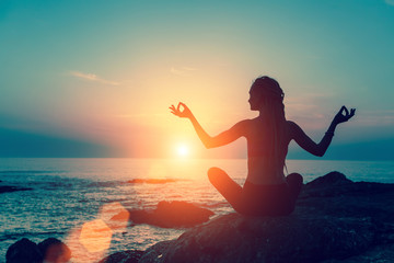 Meditation girl on the sea during sunset. Yoga silhouette.