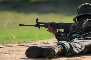 Soldier firing rifle gun to target