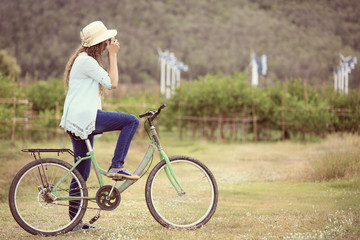 Asian woman on bicycle taking photo