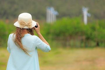 Woman taking photo of wind turbines