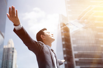 Sucess businessman in the city raising his arms, open palms, with face looking up