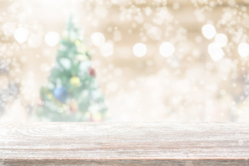 Wood table top on blur with bokeh christmas tree background with snowfall - can be used for display or montage your products