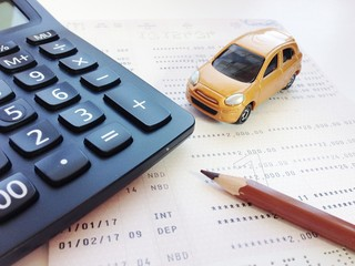 Business, finance, savings, banking or car loan concept : Miniature car model, pencil, calculator and savings account passbook or financial statement on white background