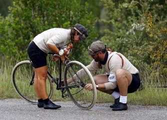 """Cyclists repair a vintage bicycle during the Strade Bianche section of the """"Eroica"""" cycling race for old bikes in Gaiole in Chianti"""
