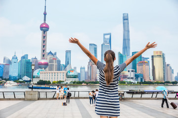 Wall Mural - Happy success person with arms up against Shanghai skyline on The Bund. China travel concept or urban lifestyle. Happiness healthy living people in modern city. Woman winning goal challenge.