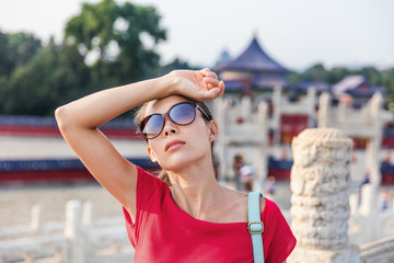 Female asian tourist exhausted during famous attraction visit vacation. Woman wearing sunglassses sweating from sun and heat exhaustion on warm summer day in Beijing, china. Asia travel destination.