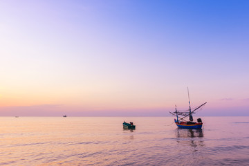 Sunrise at the Sea with fisher boats and cloudy sky