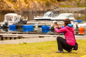 Tourist adult woman taking picture using camera.