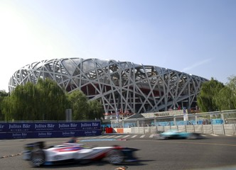 Formula E racing cars past the National Stadium, also known as the Bird's Nest, in the non-qualifying practice session during the Formula E Championship race in Beijing