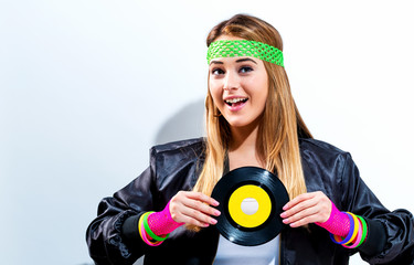 Wall Mural - Woman with a vinyl record in 1980's fashion on a white background