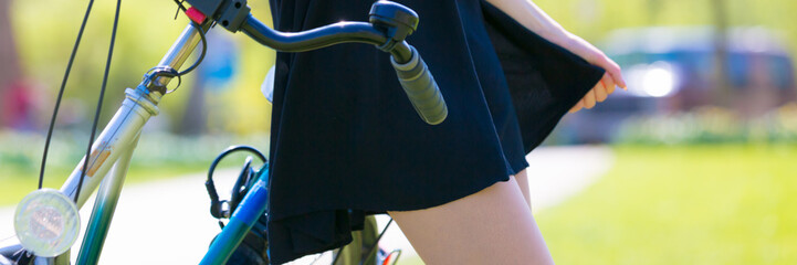 Girl next to a bicycle holds a skirt edge of a short black dress, Summer park