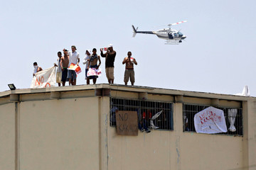 Inmates stand on the roof of the Topo Chico prison as a helicopter flies over the area during a massive riot after dozens of prisoners were transferred to other prisons, according to local media, in Monterrey