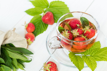 Glass cup of summer tea with fresh strawberry. Green leaves. Fresh mint. White wooden table. Shallow depth of field.