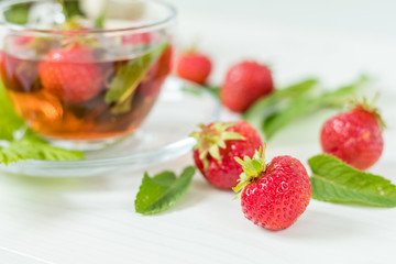 Fresh strawberry. Glass cup of summer tea with fresh strawberry. Green leaves. Fresh mint. White wooden table. Shallow depth of field.