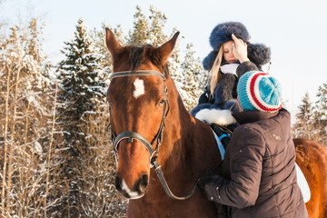 Small girl, horse trainer and horse in a winter