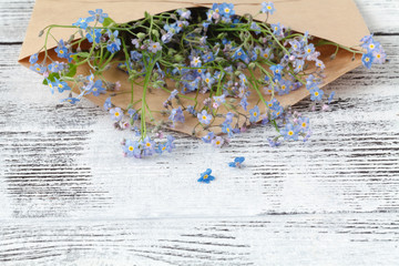 envelope with flowers forget-me-nots on wooden background