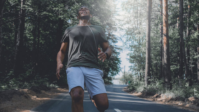 African American man stops after sprinting on a forest road. Young athletic male exercising outdoors